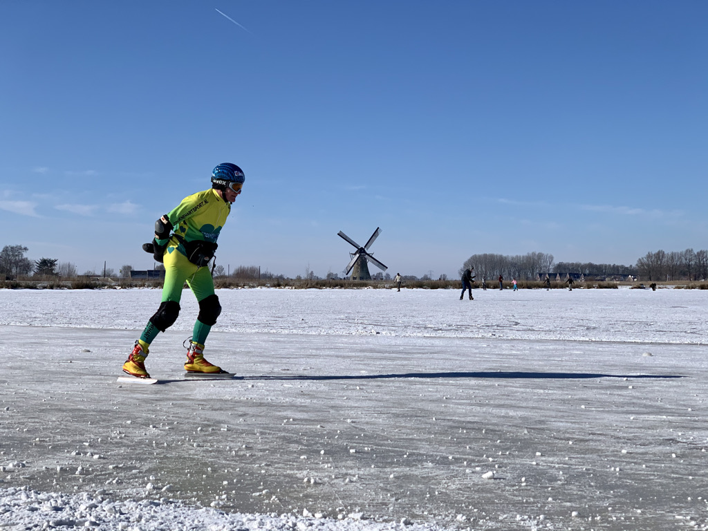 Skaters on a frozen lake with farms and a windmill in the background